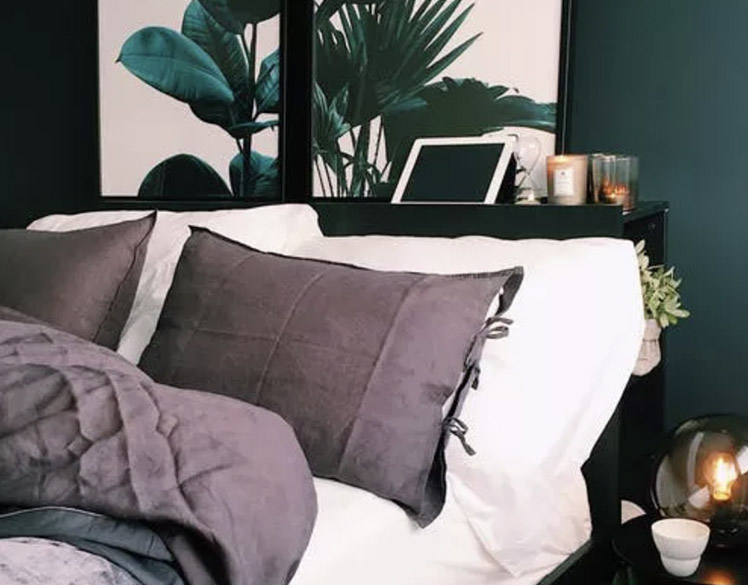 a bed with a bed head and some art