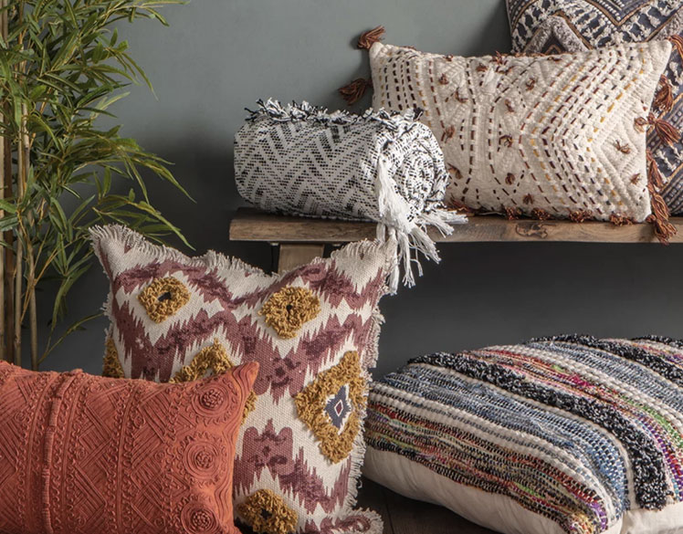 Multiple cushions against a wall, with a plant