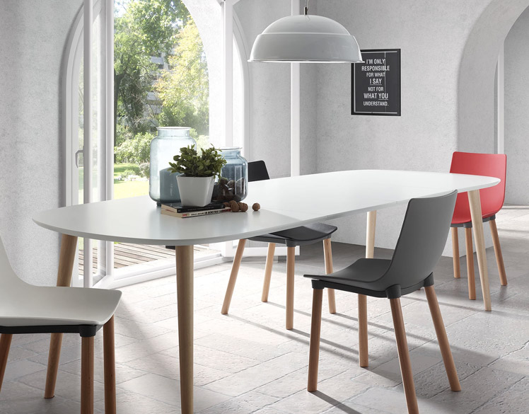 A modern dining table with chairs and a view into an outdoor garden