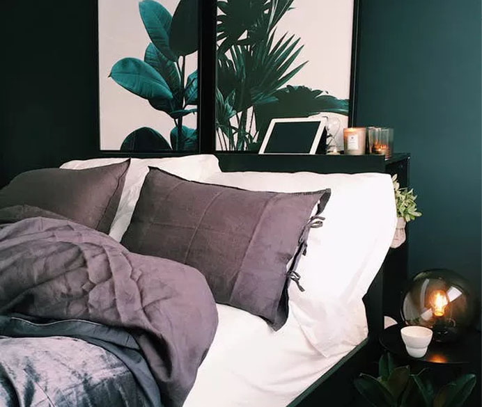 A bed with pillows, side table and feature paintings