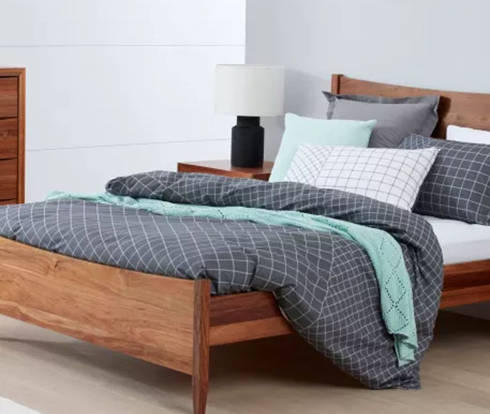 A bed on a wooden frame, with the sheets slightly pulled back to reveal pillows