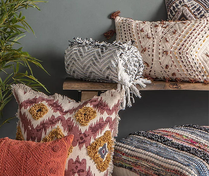 Multiple pillows and a throw rug against a wall
